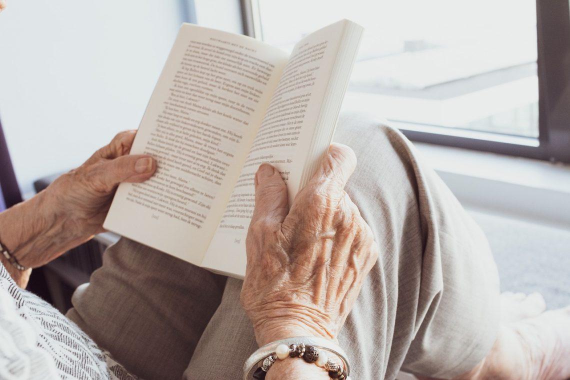 Eine ältere Dame sitzt am Fenster ihres Hauses ein Buch lesend.