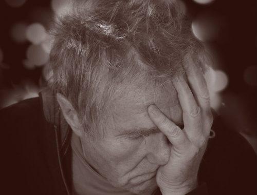 Ein älterer Mann hält bei gesenktem Kopf eine Hand verzweifelt vor das Gesicht.