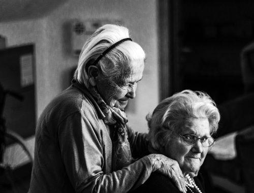 Zwei ältere Damen in schwarz und weiß: Eine sitzend, die andere hinter ihr stehend, legt der Sitzenden die Hand auf die Schuktzer. Beide wirken freundschaftlich verbunden.